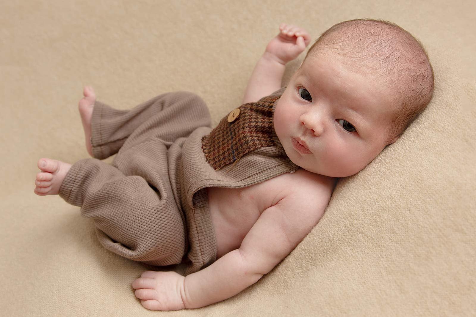 newborn baby boy in dungarees by Newborn Photographer Bradford