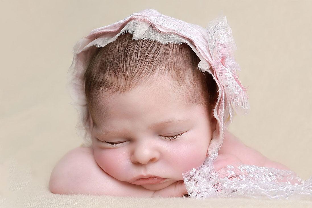 Baby girl in pink bonnet by Newborn Photographer Bradford