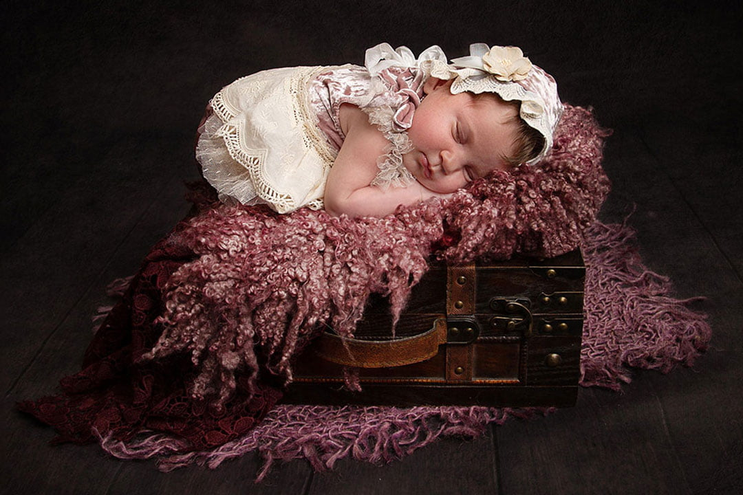 baby girl sleeping on bed with pink fluff by Newborn Photographer Bradford
