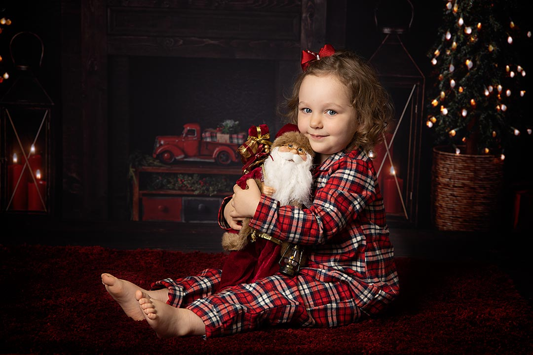 smiley little girl clutching santa